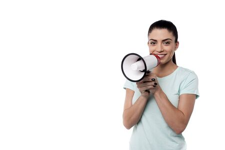 casually: Smiling woman proclaiming into megaphone casually