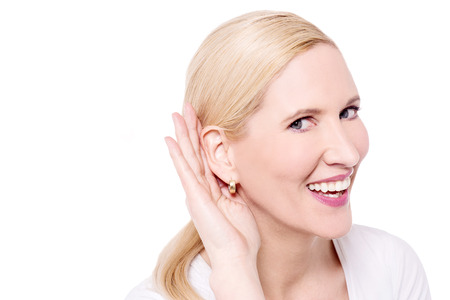 perceive: Listening woman holds her hand near ear