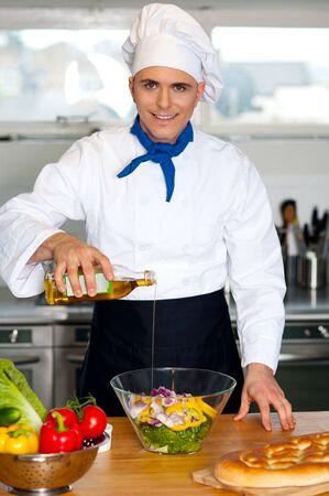 Image of male chef pouring oil into vegetable salad in the kitchen