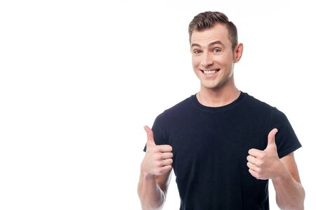 posing  agree: Smiling man showing double thumbs up gesture Stock Photo