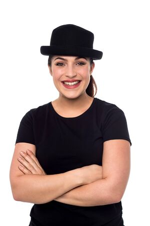 folded arms: Smiling young woman with hat and folded arms Stock Photo