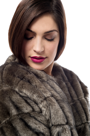 Stylish young woman in fur coat, looking down.