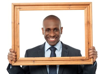 looking through frame: Smiling businessman looking through picture frame over white