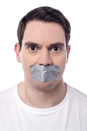 silenced: Angry man mouth covered by masking tape Stock Photo