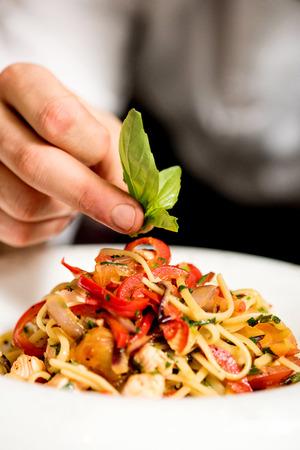 Close up of chef hand decorating pasta salad