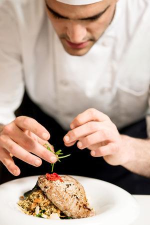 negocios comida: Cerca de chef decorar comida de pescado en la cocina Foto de archivo