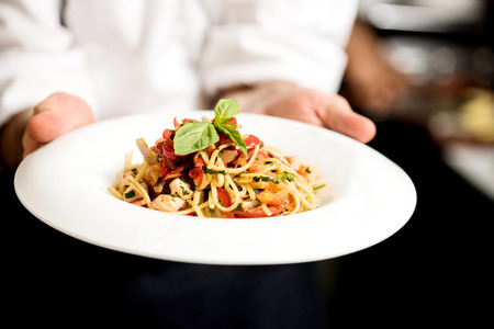 in dish: Chef hand holding tasty pasta dish Stock Photo