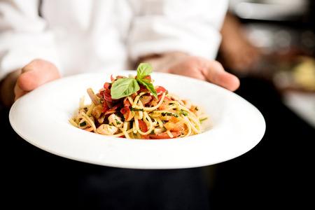 Chef hand holding tasty pasta dish Foto de archivo