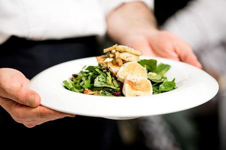 chef: Cocinero que sostiene una ensalada de queso de cabra asada
