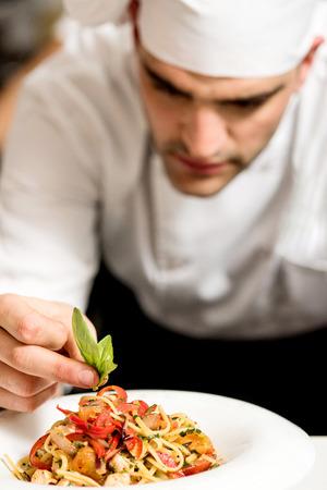 Close up cocinero de sexo masculino que adorna la ensalada de pasta