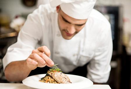 Muž šéfkuchař garnishing jeho jídlo, připraven sloužit
