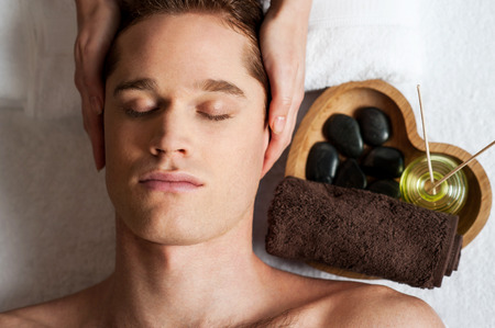 day spa: Relaxed man getting a face  massage at day spa Stock Photo