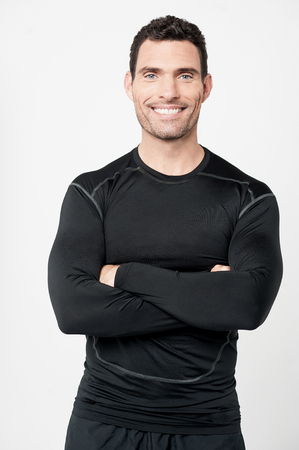 personal trainer: Confident personal trainer smiling over grey