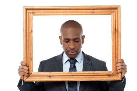 worried businessman: Worried businessman looking down with picture frame Stock Photo