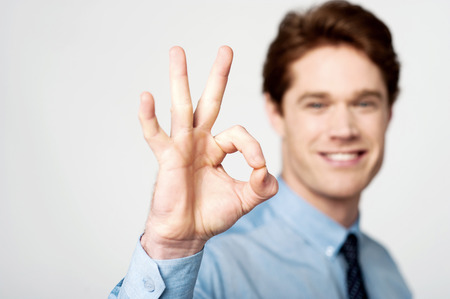 posing  agree: Happy young executive gesturing OK sign Stock Photo