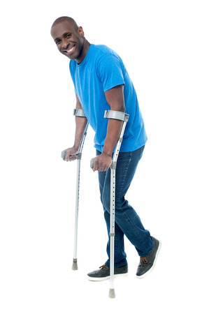 crutches: Happy middle aged man trying to walk with crutches