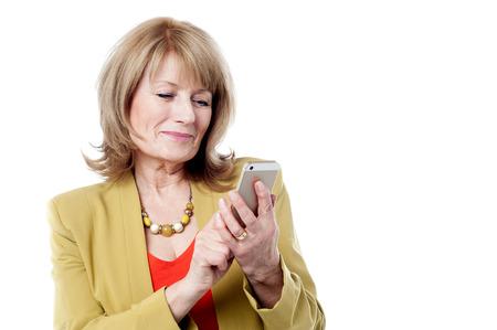 beautiful mature woman: Mature woman dialing on a smart phone