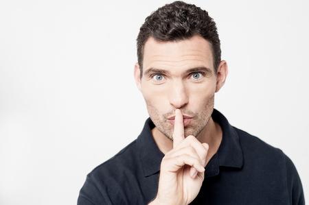 shush: Serious man keeping finger on her lips Stock Photo