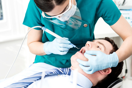 mouth cavity: Male with open mouth during oral checkup at dentist Stock Photo