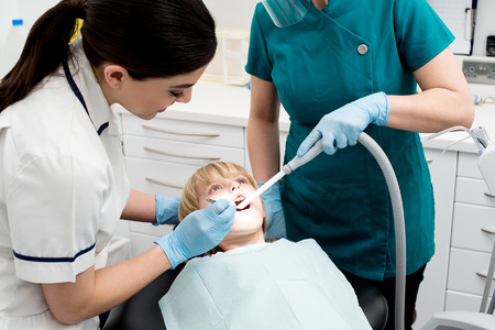 curing: Dentist and assistant curing little girl