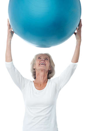 holding up: Senior woman holding up the exercise ball