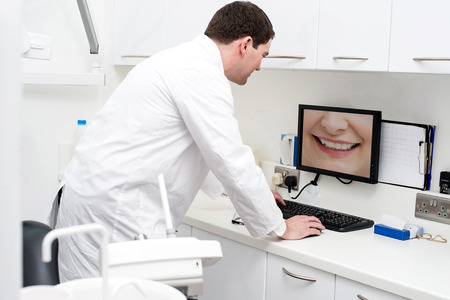 a dentist: Dentist checking patient teeth in computer screen