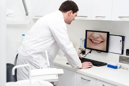 dentist: Dentist checking patient teeth in computer screen
