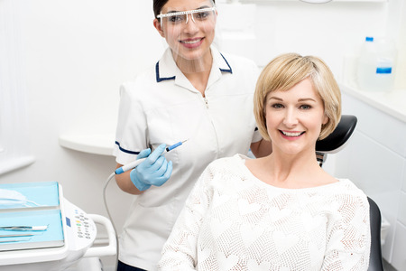 oral care: Happy woman patient sitting at stomatology clinic Stock Photo