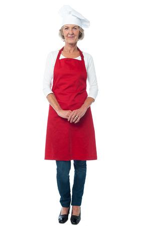 full length: Volledige lengte van de oude vrouw chef-kok met gevouwen handen