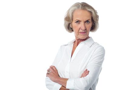 Ernstige volwassen vrouw stellen over wit Stockfoto
