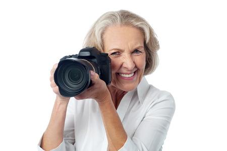 say cheese: Senior woman taking photos with DSLR camera Stock Photo