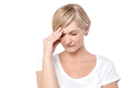 headaches: Worried woman holding her head, migraine