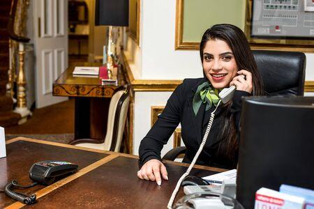 recepcionista: Estilo sonriente recepcionista habla en el teléfono