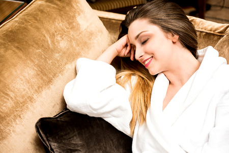 luxurious sofa: Smiling young woman laying on luxurious sofa