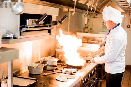 chef cocinando: Cocinero de sexo masculino que cocina en una sartén en una cocina