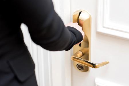 cerrar puerta: Mano de la mujer de insertar la tarjeta llave en la cerradura electrónica