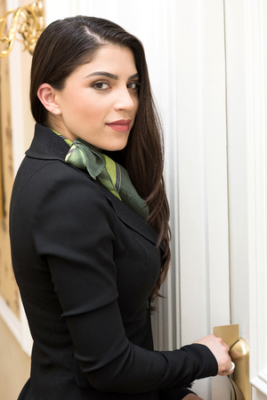 carves: Young chambermaid standing in front of a room door