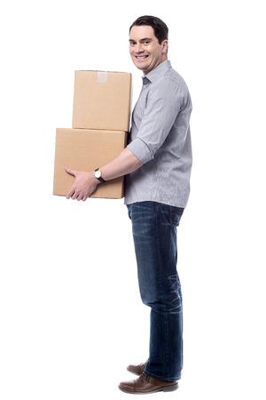 Sideways of casual man handling cardboard boxes