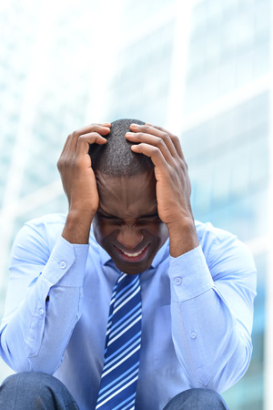 male headache: Frustrated businessman sitting in office steps