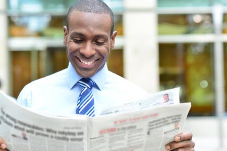 periodicos: Feliz ejecutivo macho leyendo un periódico