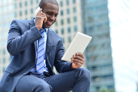 african american male: Businessman looking his tablet while talking on mobile