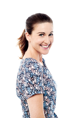 side pose: Side pose smiling woman looking at camera. Stock Photo