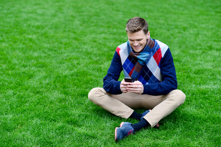 messaging: Young man playing with his mobile at park
