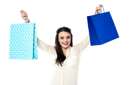 holding up: Excited girl holding up her shopping bags Stock Photo