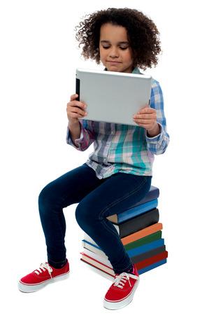 little girl sitting: Little girl sitting on books with digital tablet