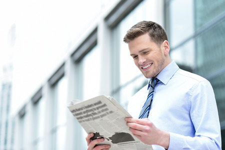joyful businessman: Sideways executive interestingly reading news paper