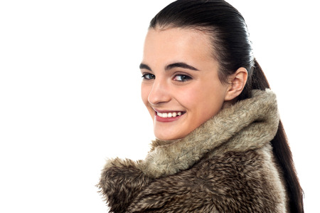looking over shoulder: Teen girl in fur jacket, looking over shoulder Stock Photo