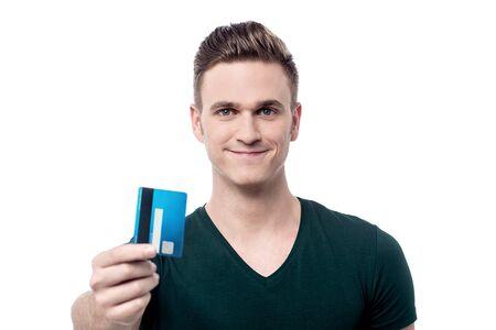 debit card: Young man showing debit card to camera Stock Photo