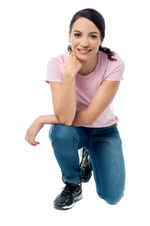 crouched: Casual woman crouched down on knees over white