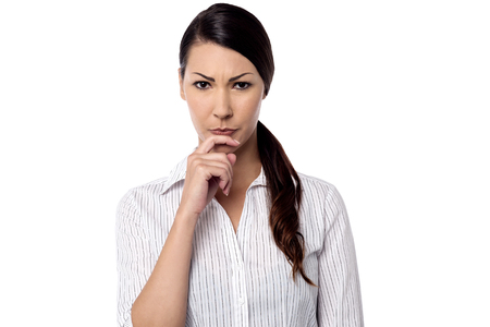 skepticism: Pondering woman with hand on her chin Stock Photo